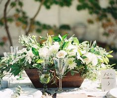Go au naturel with table centerpieces filled with lush greens and white blooms in a wooden vessel.