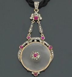 A rock crystal, ruby and diamond pendant with a black cord  mounted in silver-topped eighteen karat gold; pendant dimensions: 2 5/8 x 1 5/16in.; length: 24 3/4in.