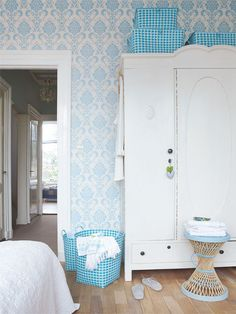 Blue and white wallpapered bedroom
