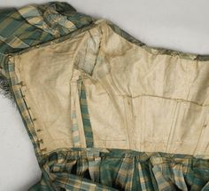 """bodice interior - sleeve detail - 1850s silk taffeta dress, included  button-in long sleeves, wide neckline adjustable with drawstrings, sleeves ruched at top and trimmed with silk fringe at hem, dress has back hook & eye closure, bodice boned, lined with ecru linen, skirt has small watch pocket in side front seam, hem faced with wide border of polished green cotton & green braid at hem, bust: 32""""; waist: 22""""; shoulder to hem: 56""""; shoulder to waist: 12.5"""""""