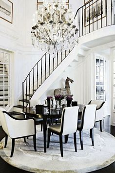 A dramatic staircase is taken to the next level with a black-and-white color scheme and an over-the-top chandelier.