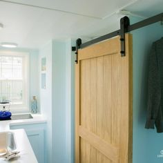 84 Tiny Living Blue Shonsie Tiny House | Blue epoxy floor, light blue walls, and white ceiling snd cabinetry