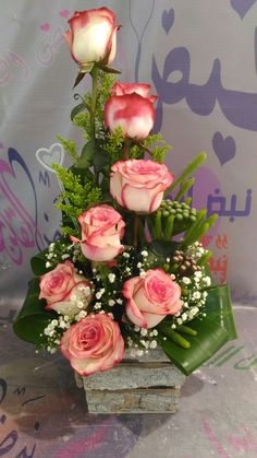 The shape of the arrangement is is triangular. The fill flowers are pink orange roses.