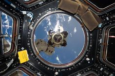 The end effector — or grappler — at the end of the Space Station's Canadarm 2 robotic arm is visible out the main window of the Cupola, with a view of our beautiful blue planet below. Credit: NASA.