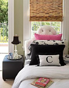 Ken Fulk - Chic teen girl's bedroom design with bamboo roman shade, silk white tufted headboard, leather cube end table, silver tray, crystal lamp with black shade, pink black pillows, sisal rug and green paint wall color. green pink black white girls bedroom colors.