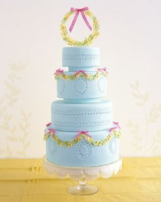 Guests will be enchanted with a pale-blue wedding cake draped in garlands of tiny leaves and delicate paper bows.