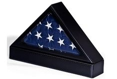 Military flag display cases, like a display for a national ensign, are ideal for a memorial presentation. These wooden military flag boxes protect a banner from dust and dirt, yet allow the keepsake gift to be viewed. These American flag cases have a triangular shape, so a national ensign folded in the standard fashion fits perfectly in the holder. The included pedestal adds height to the box and makes the display more visible when placed on a shelf