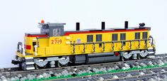 Falk (bricknerd, top) and Peter Norman (swoofty, bottom) performed a trans-Atlantic (respectively in Berlin and LA) LEGO co-build with this cute twinset of Union Pacific (UP) locomotives. Both models are excellent demonstrations of all the techniques good train builders are known for, with clever and varied grilles and other texturing details, as well as some …