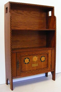 LX_26 Arts and Crafts cabinet by Shapland & Petter  Arts and Crafts free standing cabinet in oak with ebony and boxwood chequered inlay and stylised inlaid flower design.   Shapland & Petter Barnstable   Circa 1900
