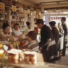 Interieur van een kruidenierswinkel waar je nog van achter de toonbank wordt geholpen. Drie medewerksters achter de toonbank, vijf klanten in de winkel. Nederland, zonder jaartal [1960-1970].