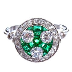 Three Old European cut diamonds weighing ~0.70 carats total set in a bed of calibrated cut emerald with a round diamond border of ~0.30 carats in a remarkable platinum fancy basket setting