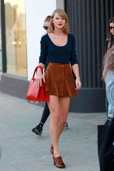 Taylor Swift, Blusa azul marinho, saia de camurça caramelo, oxford marrom