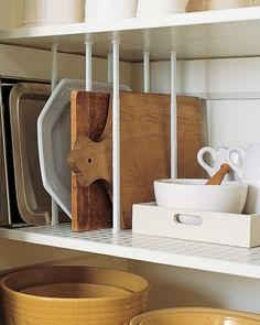 Storing baking sheets, cutting boards, and sturdy platters upright on kitchen shelves frees space and keeps you from having to lift a heavy stack when you need only one item. Create dividers for them using tension curtain rods. Buy rods to fit the space, and position pairs of them at intervals. Twist to tighten.