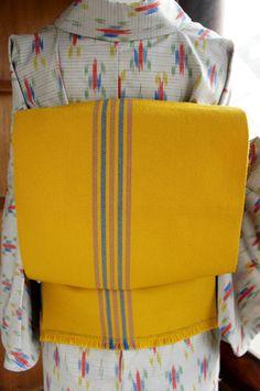 からし色の地に空色とグレーのモダンストライプが織り出されたウールの名古屋帯です。
