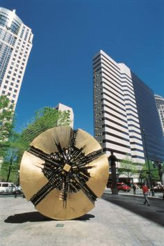 """""""Il Grande Disco"""" a bronze sculpure stands in front of the Bank of America Plaza. The large, coin-shaped piece with dark edges was created for the space by Italian sculptor Arnaldo Pomodoro and was installed in October 1974."""