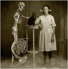 Woman with sea shells, a black cat on a table, and a skeleton holding a french horn