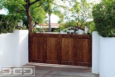 Updating your historical home's curb appeal while increasing security and adding value to your property can be achieved with a <b>custom designed and manufactured driveway gate</b> by <b>Dynamic Garage Door</b>. Featured in this photo is the street view of a custom <b>Spanish Colonial driveway gate</b> that was especially designed and handcrafted for this historical <b>Los Angeles, CA</b> residence. The <b>driveway gate design</b> is simple but the hand wire-brushing and alder wood natural…