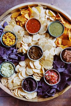 EPIC Chips and Salsa Board, the perfect potluck party food! Enjoy flavored salsas, guacamole, corn and beans dips, sour cream, served with a variety of corn and tortilla chips! #charcuterie #mexicanboard #chipsandsalsa