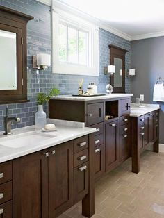 Dual Vanity with Extra Storage while sophisticated design. Elevated storage in the middle cleverly conceals outlets and trash basket. Glass wall tile adds color and shine.