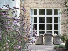 pale lime mortar red brick chalky shades | rattan dining chairs and verbena | Domus Aurea | Exclusieve Villabouw