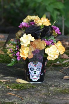Die Miedo Skull Bouquet - Gillespie Florists, Indianapolis IN The De Miedo Skull bouquet is a Sugar Skulls inspired halloween arrangement with mini-carnations, wax flower, black sheer ribbon and a keepsake Sugar Skulls pail! This cute pail is 2.75 inches in diameter and 2.80 inches high.