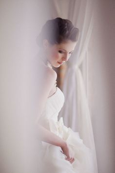 romantic // looks like you're peering at the bride from behind something, catching her in a moment.
