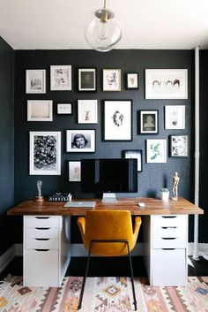 Modern home office design featuring black walls, gallery wall of white framed black and white art, wood desktop on file cabinets, a mustard yellow ;leather chair, and a southwest style patterned woven area rug - Workspace Ideas & Decor - domino.com