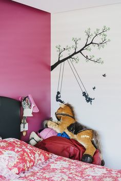 A girl's bedroom with a design on the wall.