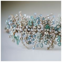 Beautiful, heavily beaded asymmetrical headdress in soft aquamarine colours of blues, greens, greys and antique silvers.  Entirely handwired using antique silver wire, this headdress is made from clusters of Swarovski glass pearls in grey and platinum, Swarovski crystals in Erinite and Grey Opal, ice blue teardrop crystals and tiny Miyuki Delica glass seed beads in frosted, opaque and metallic shades of the palest green to soft turqoise. This headpiece is the perfect choice for a bride after…