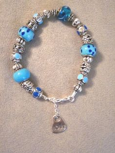 This bracelet is approximately 8 inches with lobster clasp on leather strap with a 1 inch extender from where a 'love' charm hangs. It has blue mix glass and metal beads. Goes well with jeans or a spring/summer dress. Very versatile.     http://www.newlyfoundtreasures.etsy.com