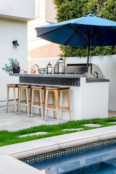 An outdoor bar island boasts decorative blue Spanish tiles that trim the outer lining of the white concrete bar under the dine in cement countertop.