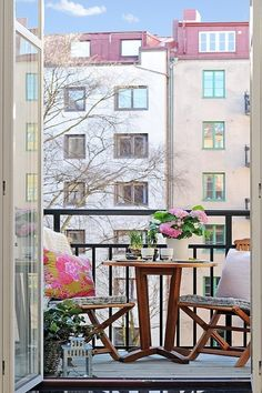 Glass door wooden rounded table flowers balcony railing city view rug plants wooden chairs floral pattern cushion