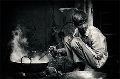The direct beam of light on the man casts bold shadows on the and everything in the background except the steam from his pot. The harshness of the light along with the man's sinister look gives the image a dark feeling.  I love how sharp the light is in the image, none of the lines blend between light and shadow.
