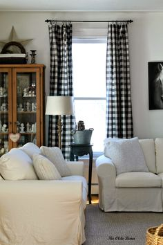 Vintage Living Room with Black White Buffalo Check Curtain Panels and White Slipcover Sofa Set. Antique Brass Floor Lamp White Shade and Grey Wool Rugs