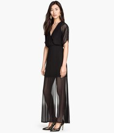 Long black dress in airy woven fabric with short sleeves. Wrap-style bodice with concealed snap fastener at front and seam at waist. Concealed zip and slit at one side. Lined.