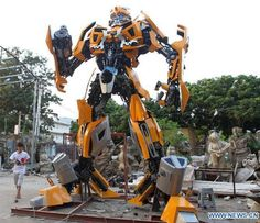 A life-size Bumblebee Transformer replica measuring 6.5 meters (around 21 feet). It is made purely from automobile parts and created by a Xiamen (southeast China's Fujian Province) artist with help from his friends to show off his love for the Transformer series. Chen Xiaodong hand-built the whole thing from three salvaged cars and other automotive parts in three months. This Bumblebee replica weighs around 4-5 tons and is equipped with cannon made from a washing machine drum.