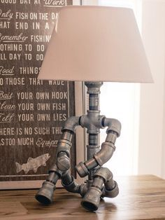 Sitting man - Table lamp made of galvanized fittings and pipes, utilizing a brass faucet as the switch.
