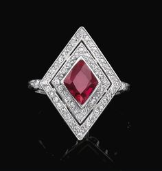 RUBY AND DIAMOND RING Collet-set with a lozenge shaped ruby framed by two rows of circular-cut diamonds, the shoulders similarly set, size 53, numbered, French assay marks. Art Deco or Art Deco style.