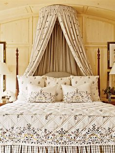 A crown canopy adds extra drama to this traditional poster bed. The soothing colors are relaxing, and while the canopy feels luxurious and stately, the yards of fabric feel cozy as well. (Photo: Tria Giovan)