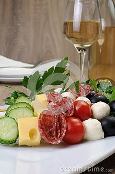 Appetizer of salami with mozzarella, olives, cherry tomatoes, cucumber and cheese on a skewer