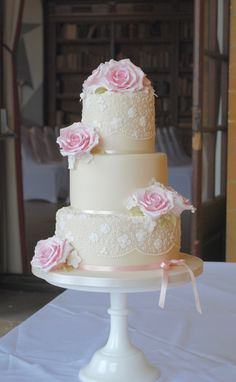 ivory wedding cake with piped lace and pink handmade sugar roses