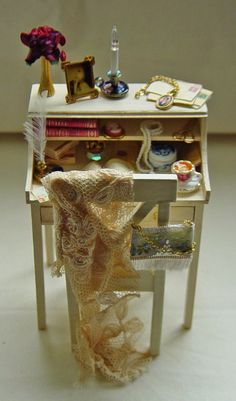 UNIQUE MINIATURES - This is a warm, antique cream aged wooden Ladies Writing Desk made to look slightly tired and worn. Filled with allsorts of items all fixed in place: books, flower, jars, love letters, cuppa with lemon, quills, jewellery, old envelopes, leather open diary, string of beads, fabulously stunning portrait on chain, etc etc etc. Genuine antique lace is used for the shawl on the chair Z