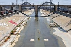 Kayakers float the Los Angeles River near the Sixth Street Bridge in downtown.