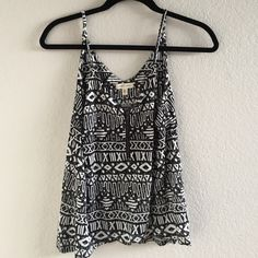 Black and white tank top Super cute black and white patterned tank top! Has never been worn before and has a nice little zipper on the front. Paired super cute with leggings and some boots! Offers welcome! Urban Outfitters Tops Tank Tops