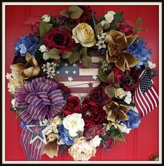 Luxury, handcrafted patriotic wreath filled with elegant artificial flowers and patriotic themed decor. This wreath is perfect as a front