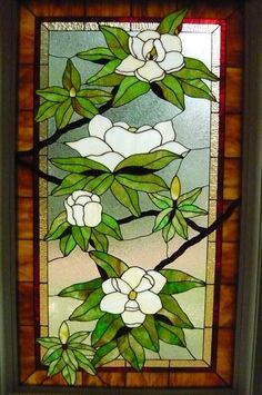 Carolina Magnolias - Magnolias are captured in stained glass in all stages of blooming from small buds to full open blossoms. Large panel measures three feet in width and five feet in height. Background is glue chip. Framing is two different ambers with small red inset to offer contrast. Designed and created by Dee Montgomery, Fort Pierce, Florida.