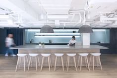 Uber Offices – Hong Kong. T point. Kitchen. Breakout. High bar bench. Feature pendants. Hay About a Stool. Muuto Under th Bell lamp. Wood. Exposed ceiling paintd white.