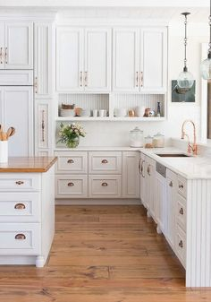 White cabinets with copper/rose gold hardware. White subway tile backsplash. Open shelving.
