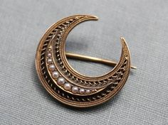 Pearl and gold crescent moon brooch.