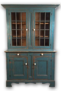 """With two glazed doors and projecting cornice. The lower section has two drawers and two panel doors, with very bold skirt and feet.  Scrapeddown to an old blue paint with replaced whalebone pulls.   c.1840-1850  87"""" x 55"""" x 20 1/2"""""""